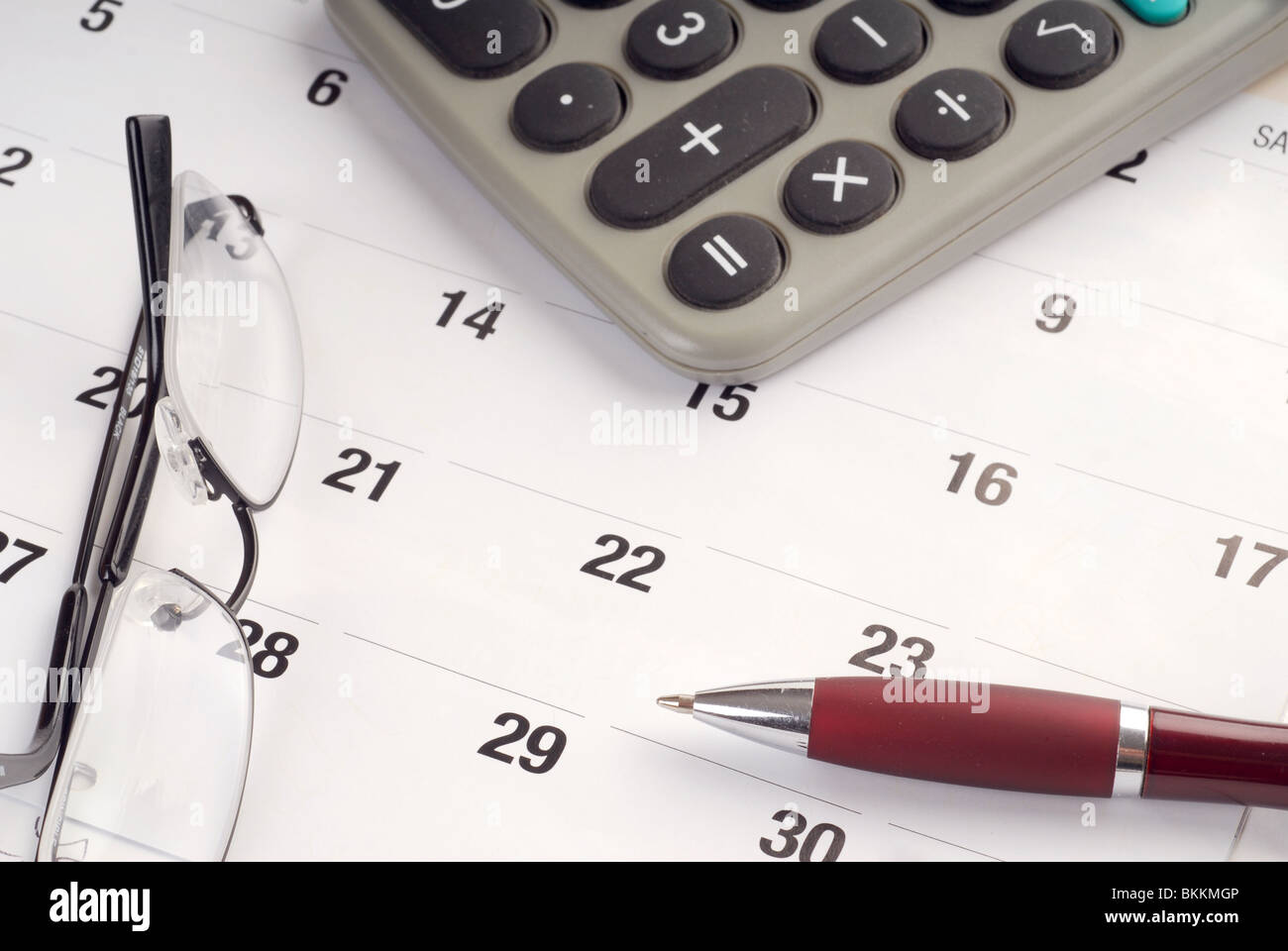 Calendar with calculator, glasses and pen on top of it - Stock Image