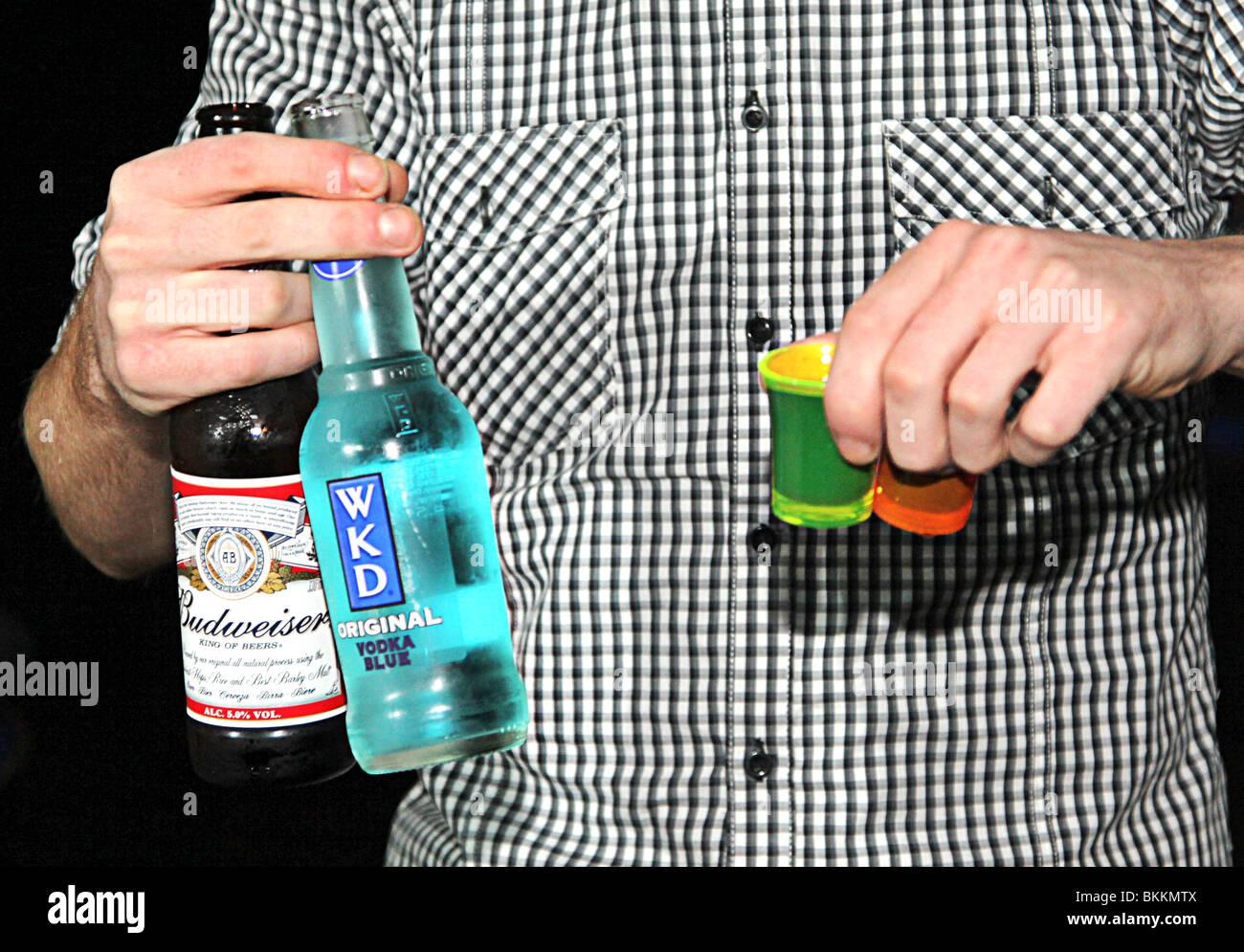 Man carrying bud, budweiser, wkd, original, drink, shots back from the bar. Underage drinking. binge drink britian - Stock Image