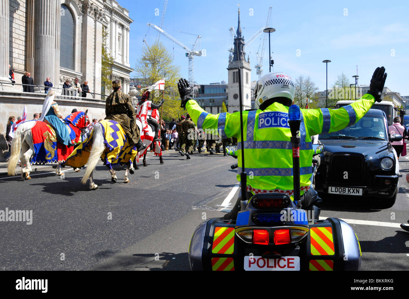 City of London motorbike policeman holding up traffic during St Georges Day parade - Stock Image