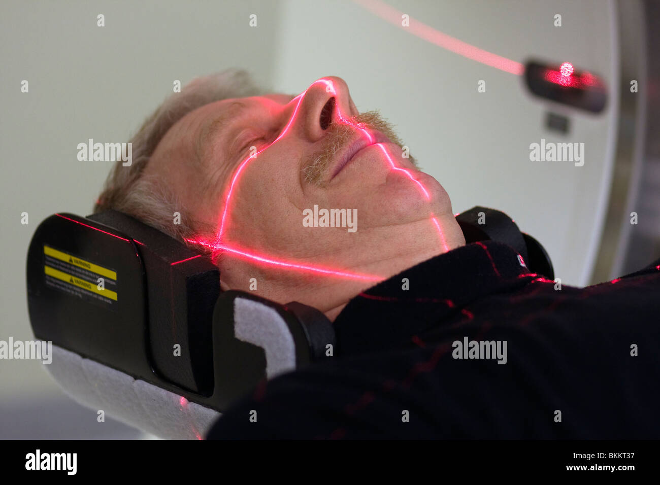 Man being adjusted to the right position before doing a CT (Computer Tomography) scan of the head. - Stock Image