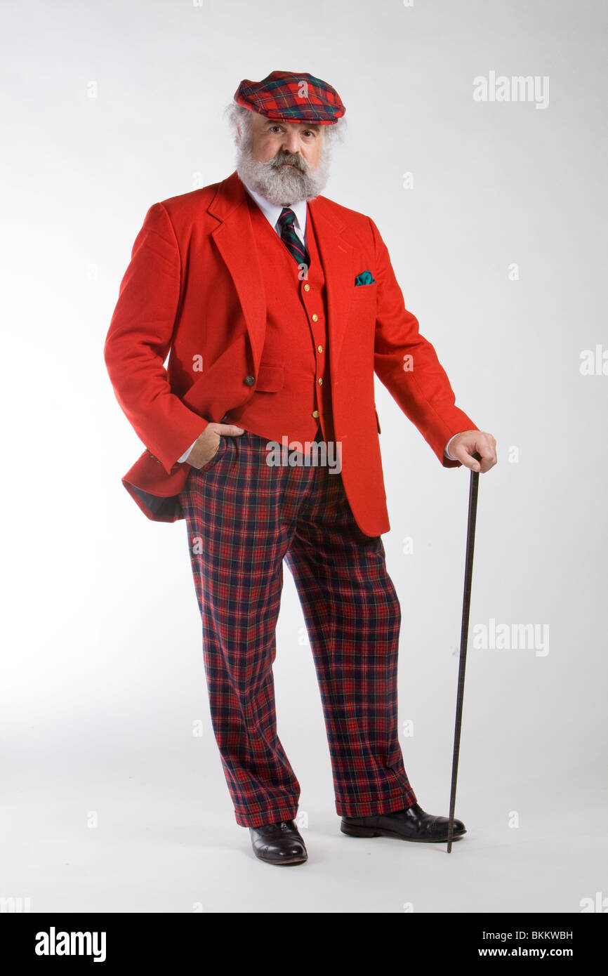 Man in a red jacket with a walking cane - Stock Image