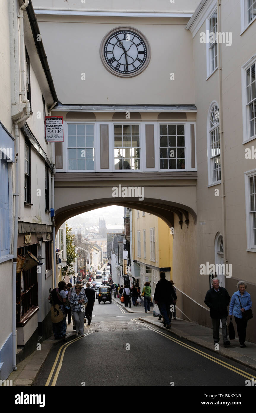 Totnes town centre shops South Devon England UK Looking down the High Street to the famous East Gate Arch - Stock Image