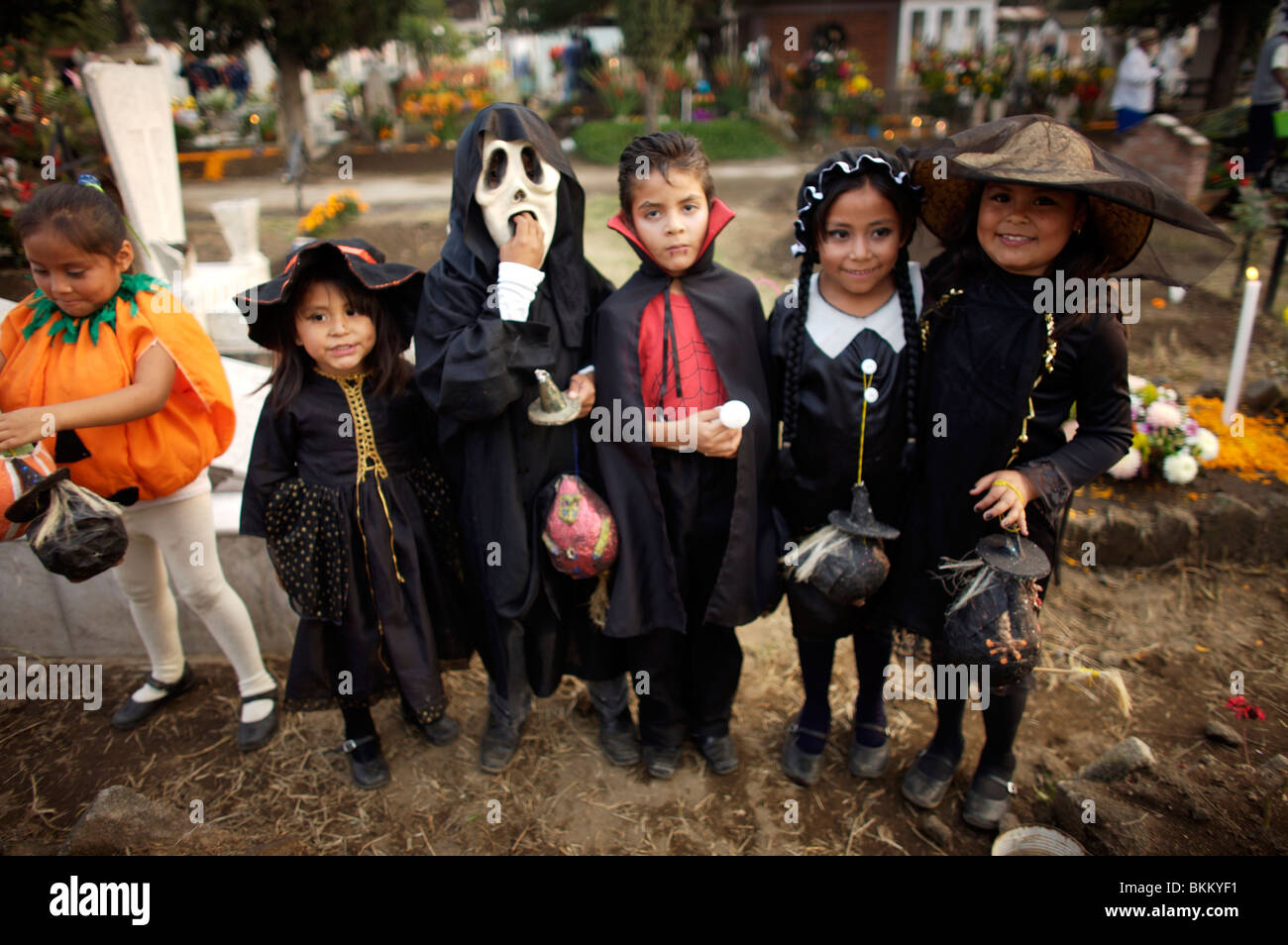 Girls and boys dressed in Halloween costumes visit the cemetery in San Gregorio Atlapulco on the outskirts of Mexico - Stock Image