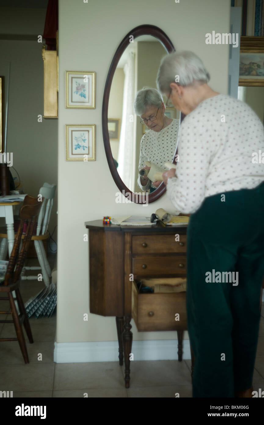 Old woman reflected in oval mirror looks at old photos she has found in small chest of drawers. - Stock Image