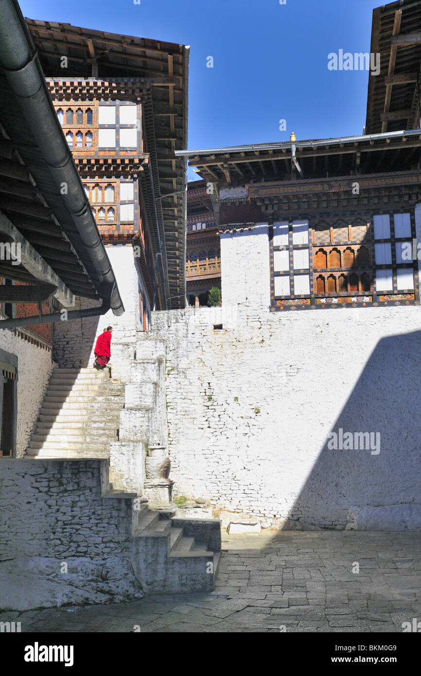 Two red robed monks climbing steps of courtyard Trongsa Dzong Bhutan - Stock Image