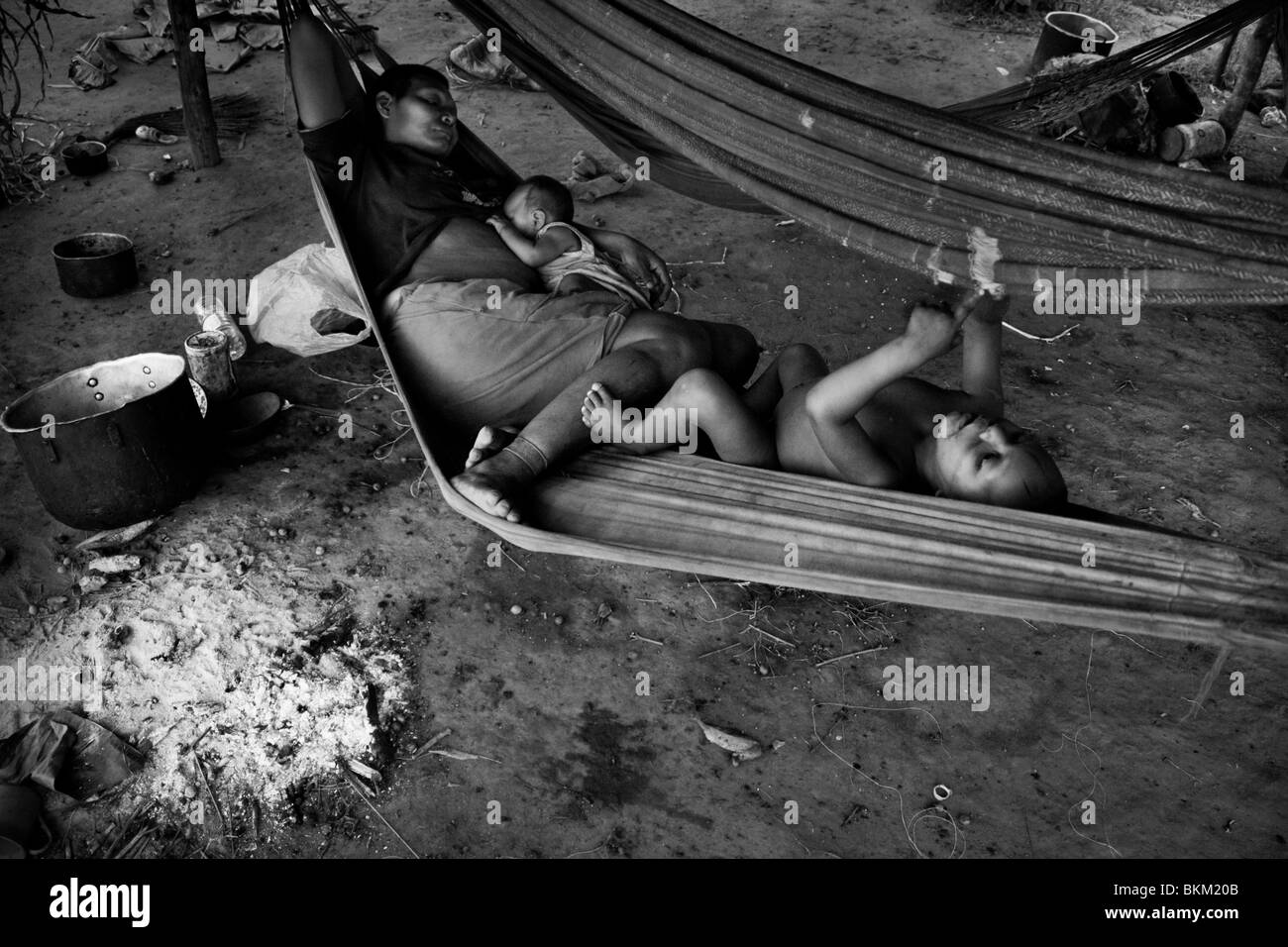 A Nukak woman with her children lies in a hammock in a refugee encampment close to San Jose del Guaviare, Colombia. - Stock Image
