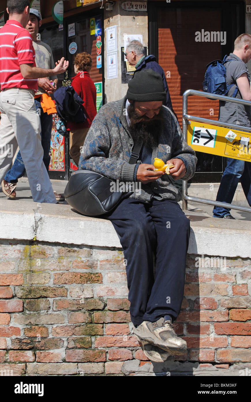 Homeless man eating an orange, Venice, Italy - Stock Image
