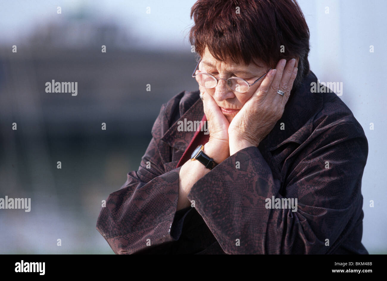 Depressed elderly woman outside contemplating in pensive mood with head in hands, looking down. - Stock Image