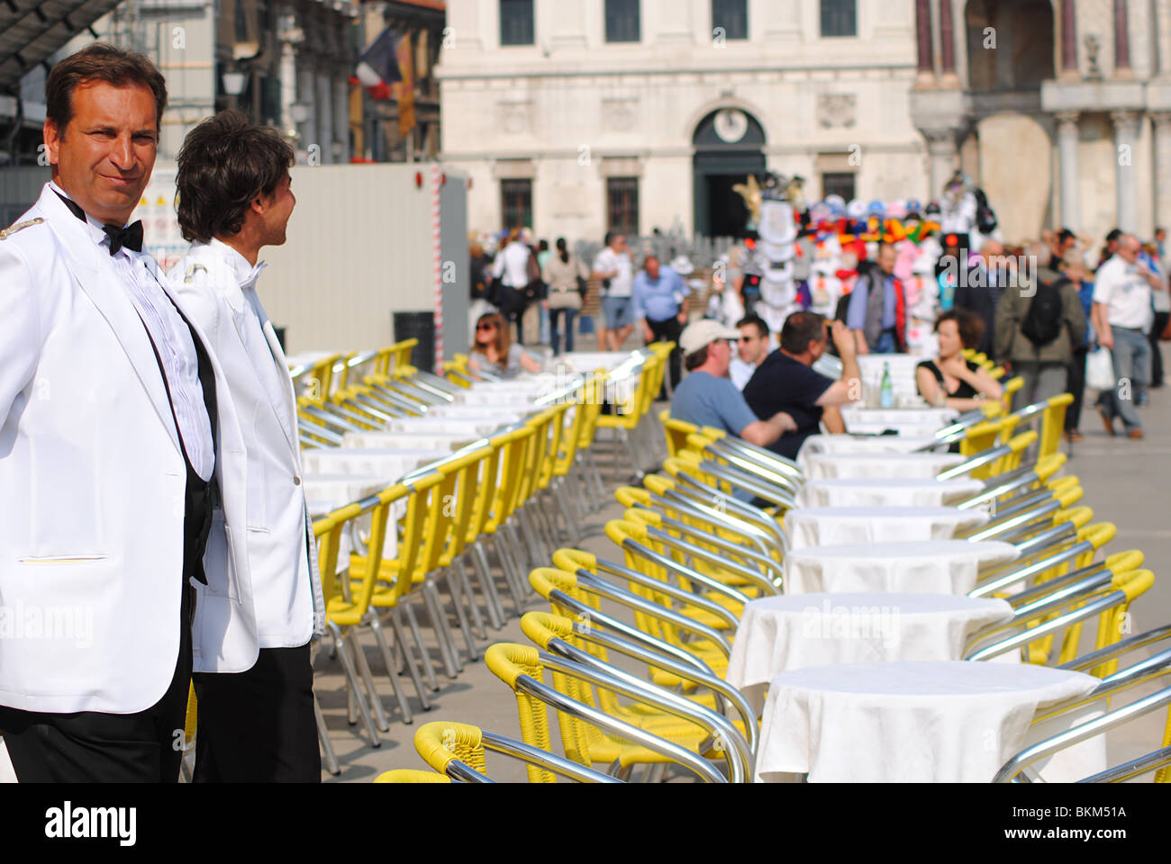 Waiters stand by empty tables at a cafe in St Mark's Square, Venice, Italy - Stock Image