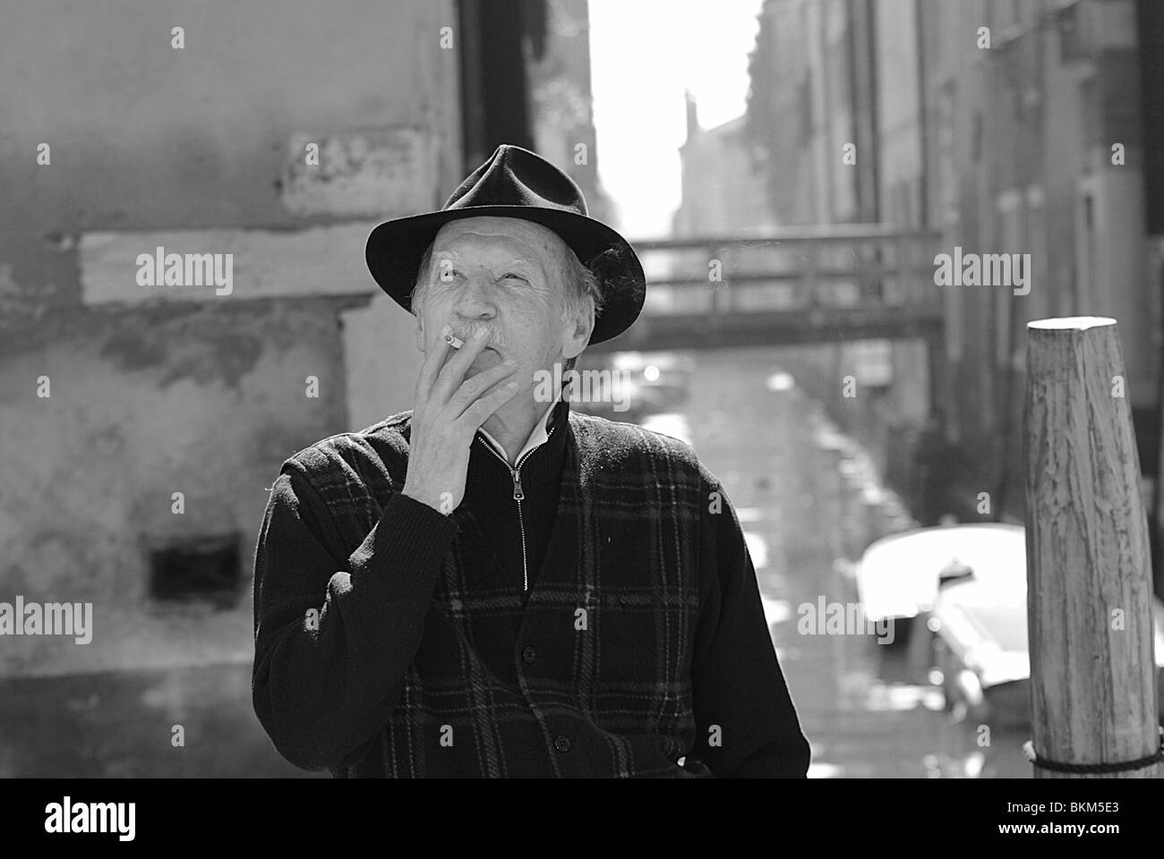 Black and white portrait of an elederly Italian man smoking a cigarette on a bridge in Venice, Italy - Stock Image