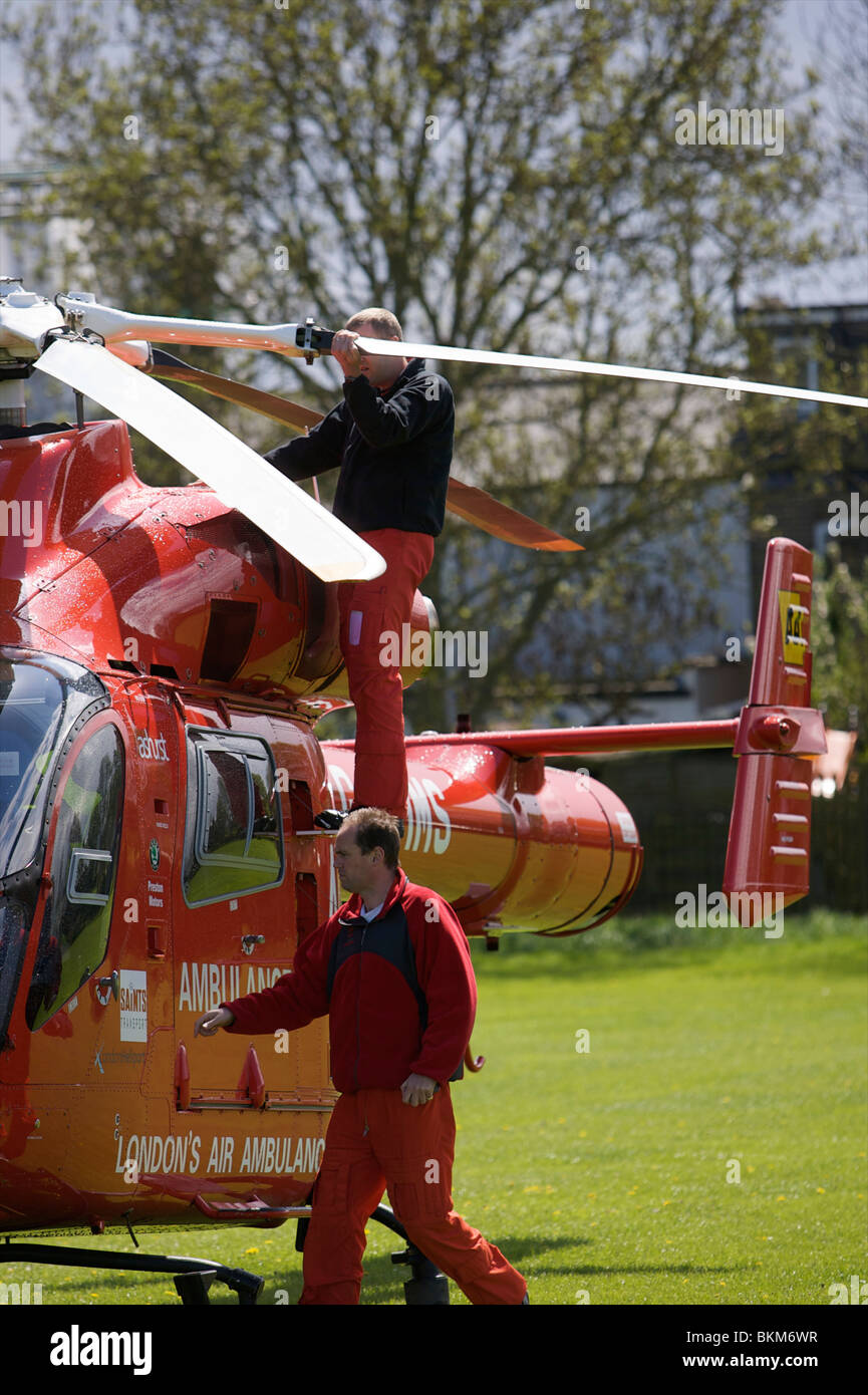 Virgin Air Ambulance lands in Enfield Park, Pilots check over aircraft prior to departure /  take off - Stock Image