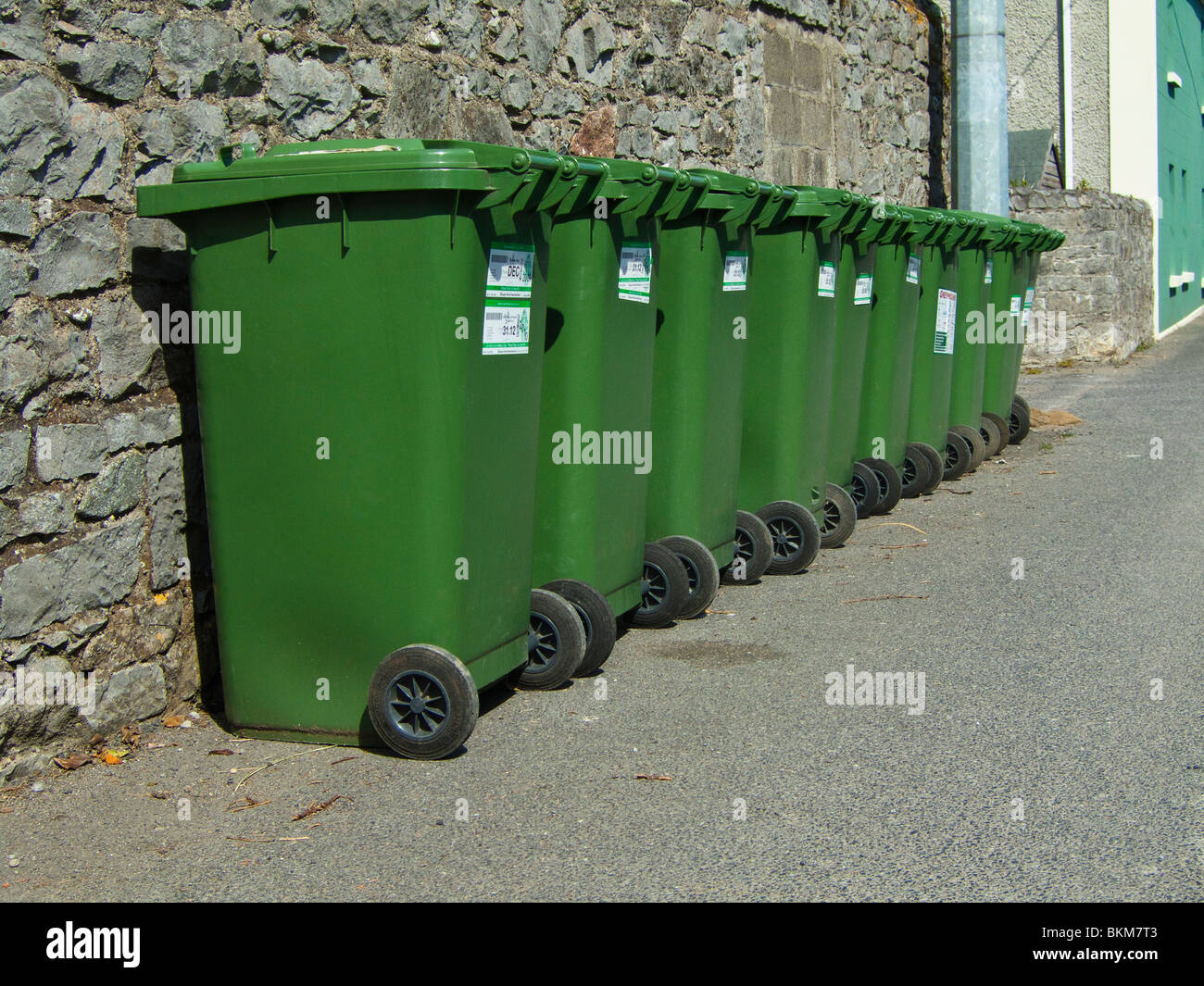 A line of green wheelie bins containing recyclable material awaiting collection - Skerries, north County Dublin, - Stock Image