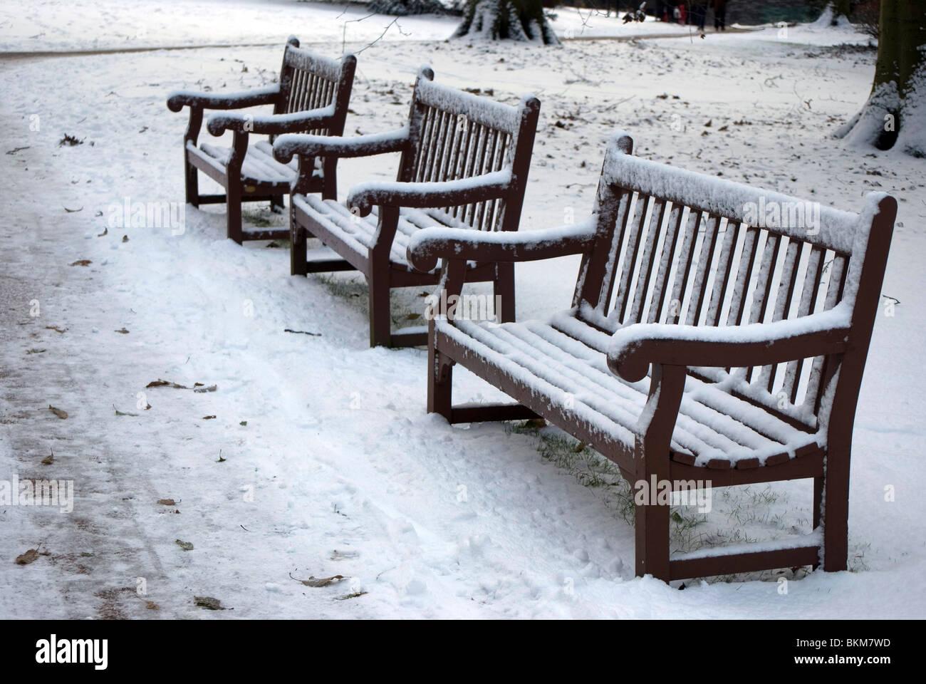 Seats (park benches) in the snow in the Royal Botanic Garden, Edinburgh, Scotland. - Stock Image