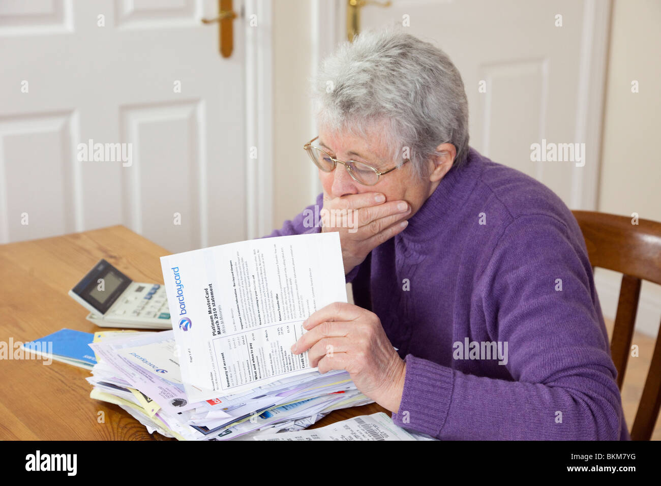 Worried senior woman retiree pensioner with a big pile of bills with hand over her mouth looking shocked at a large - Stock Image