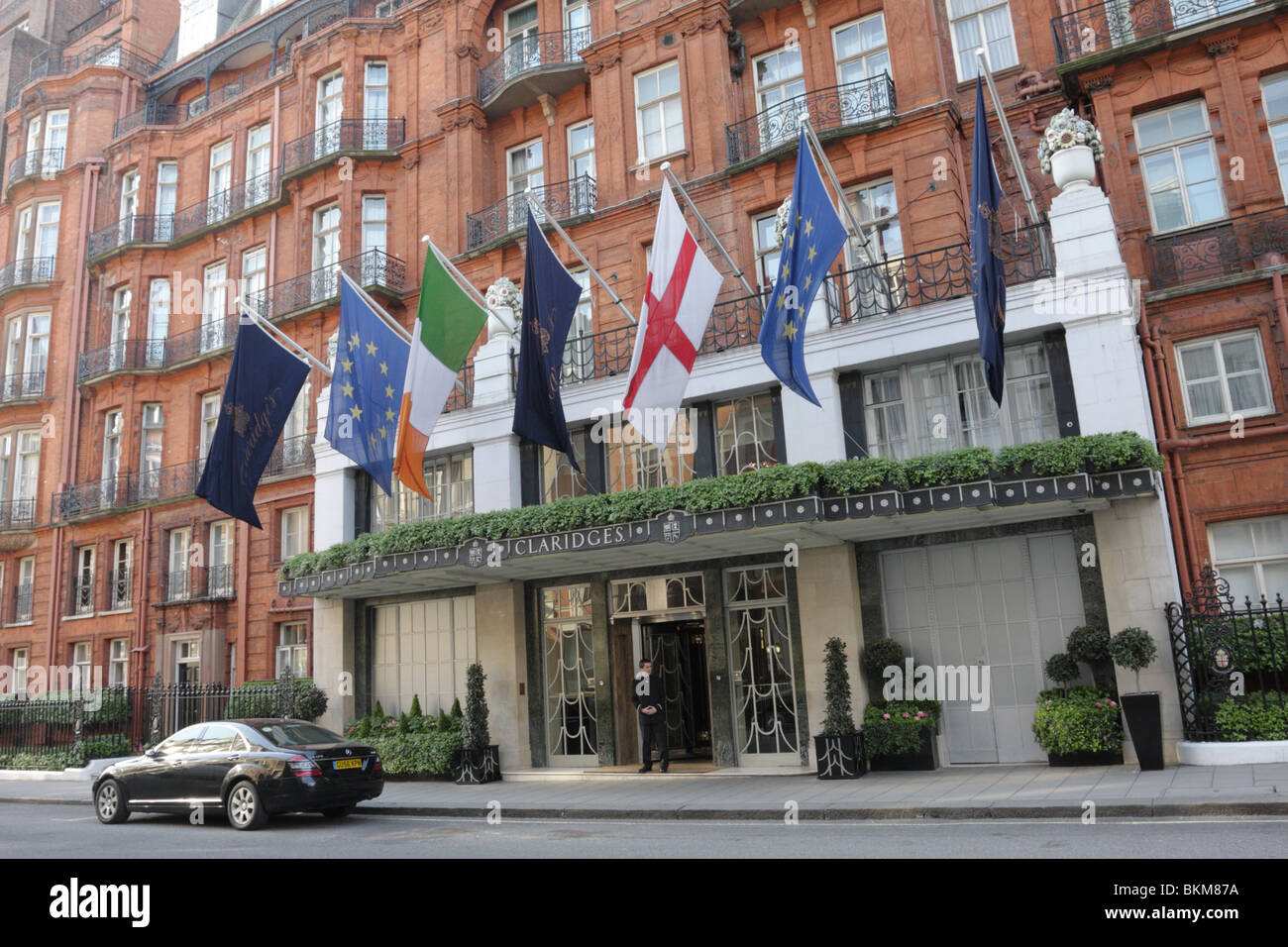 The canopied main entrance and lone doorman at the terracotta colored facade of Claridges Hotel in Brook St Mayfair. - Stock Image