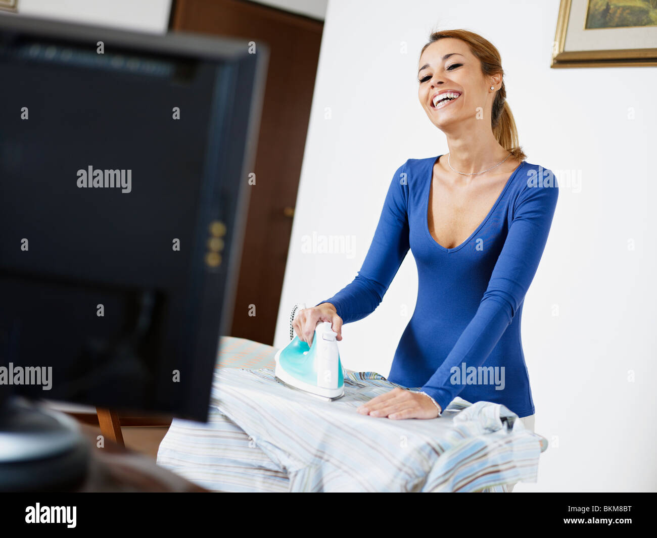 woman with iron, watching tv show and laughing - Stock Image
