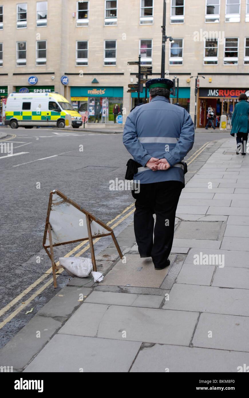 Traffic warden patrolling in Bath city centre. - Stock Image