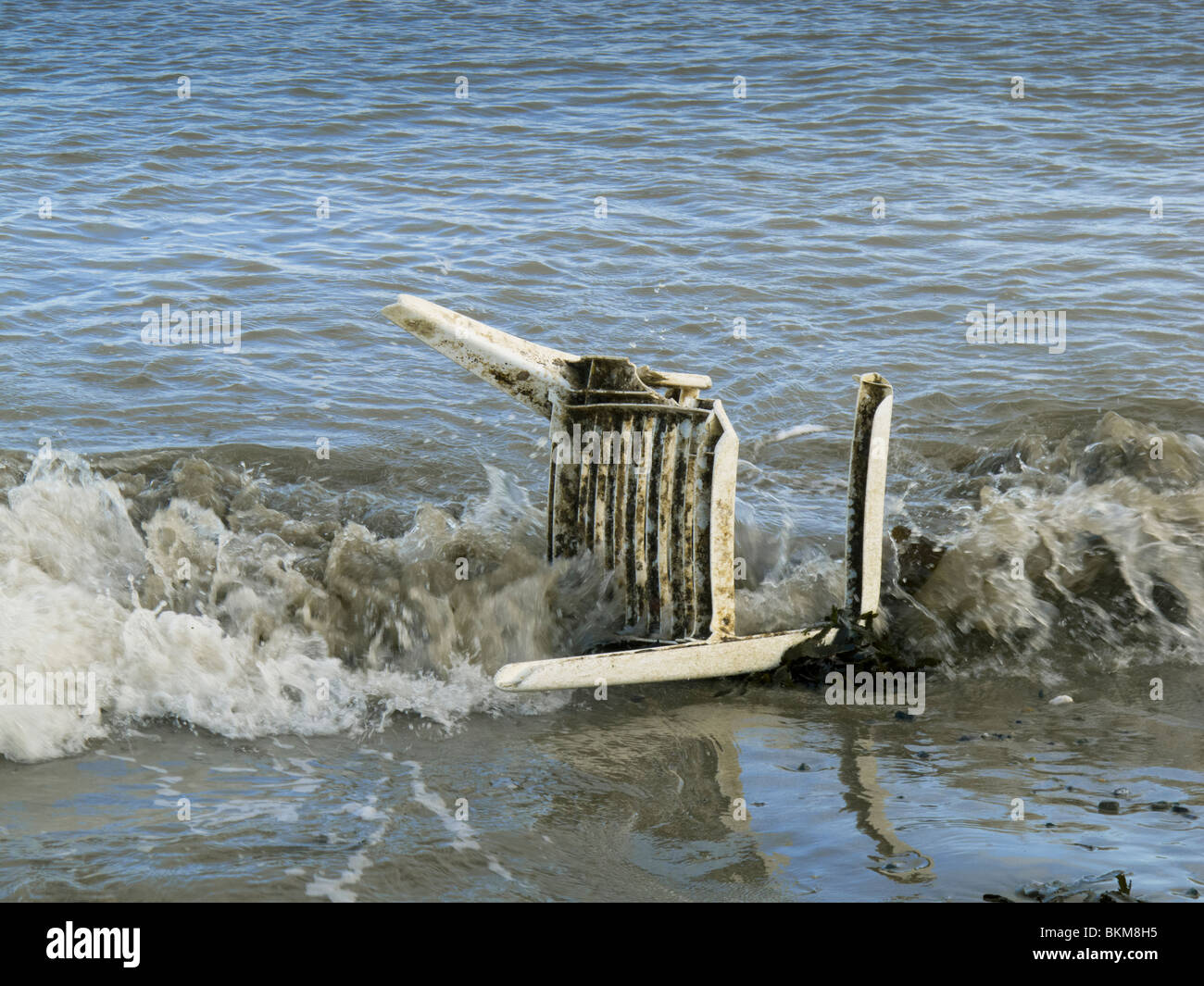 A dumped broken plastic garden chair in the sea on the beach at Skerries, county Dublin, Ireland - Stock Image