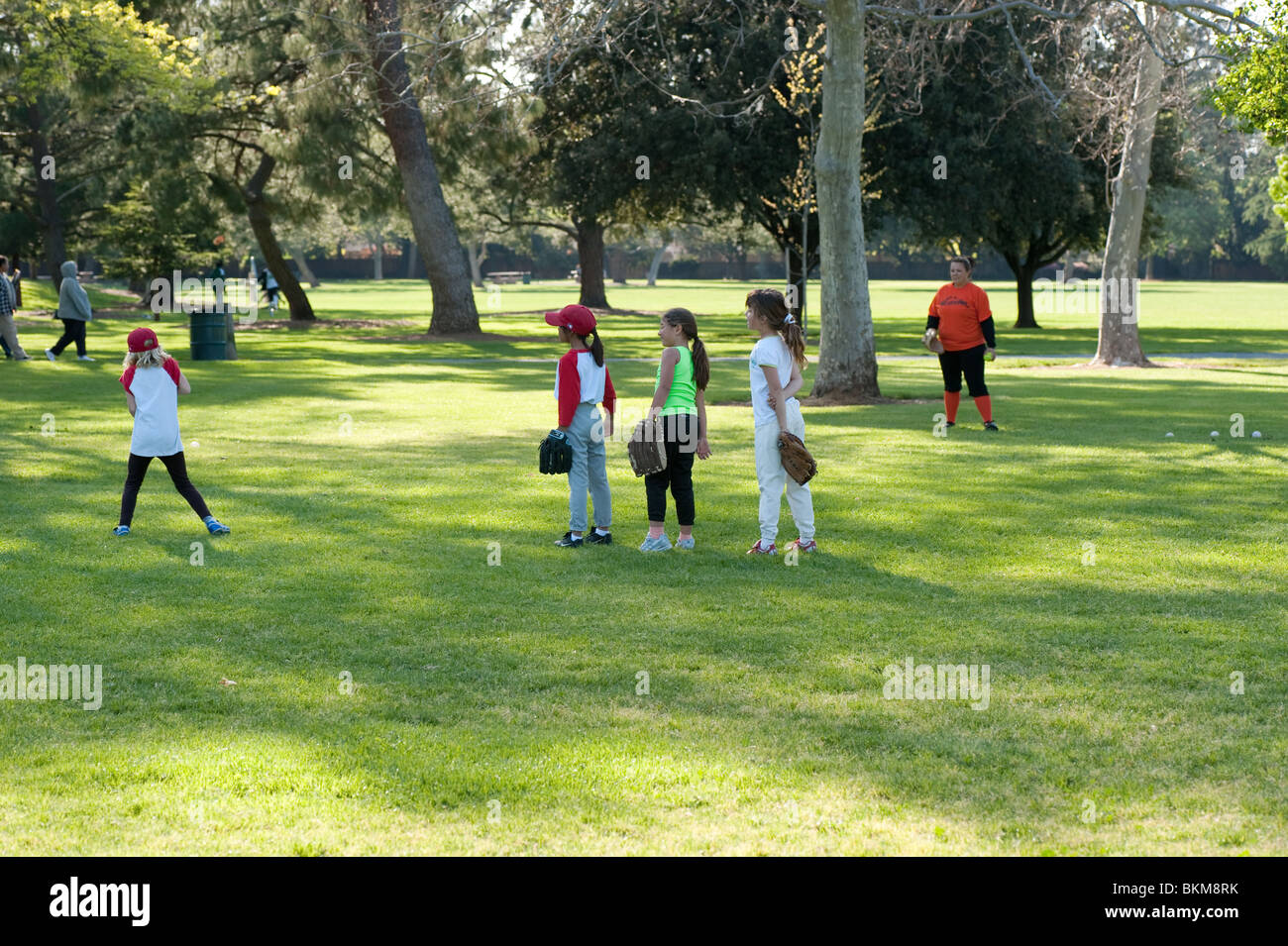 young girls lined up to catch in softball practice - Stock Image