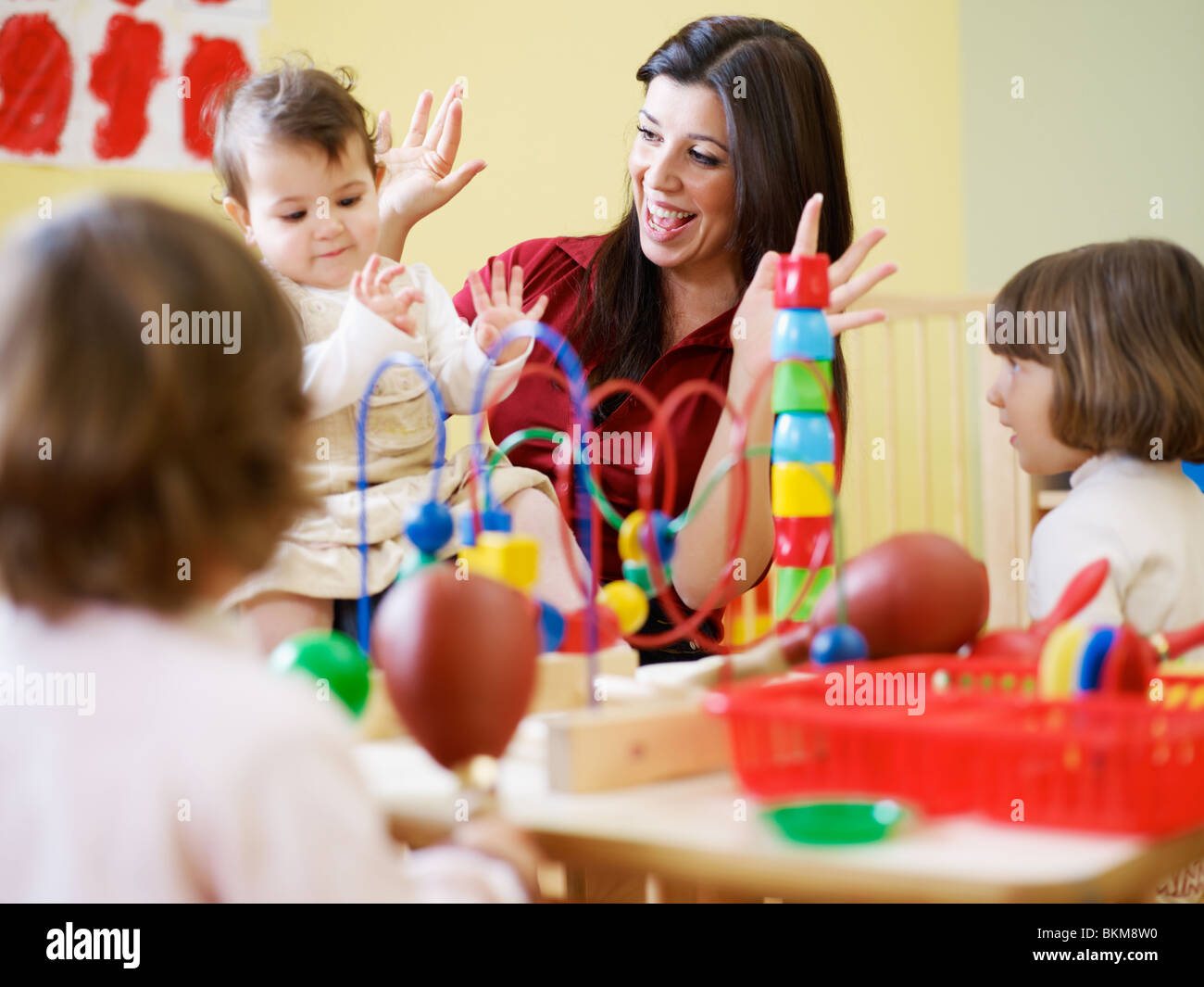 female toddler and 2-3 years girl playing in kindergarten. Horizontal shape - Stock Image
