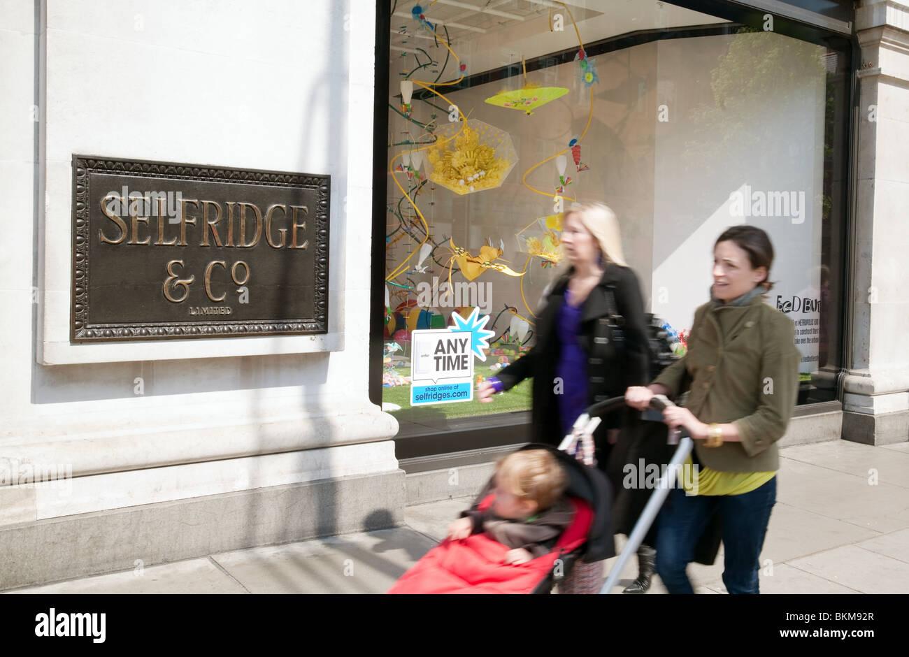 Shoppers walk past the store sign, Selfridges department store, Oxford Street, London UK - Stock Image
