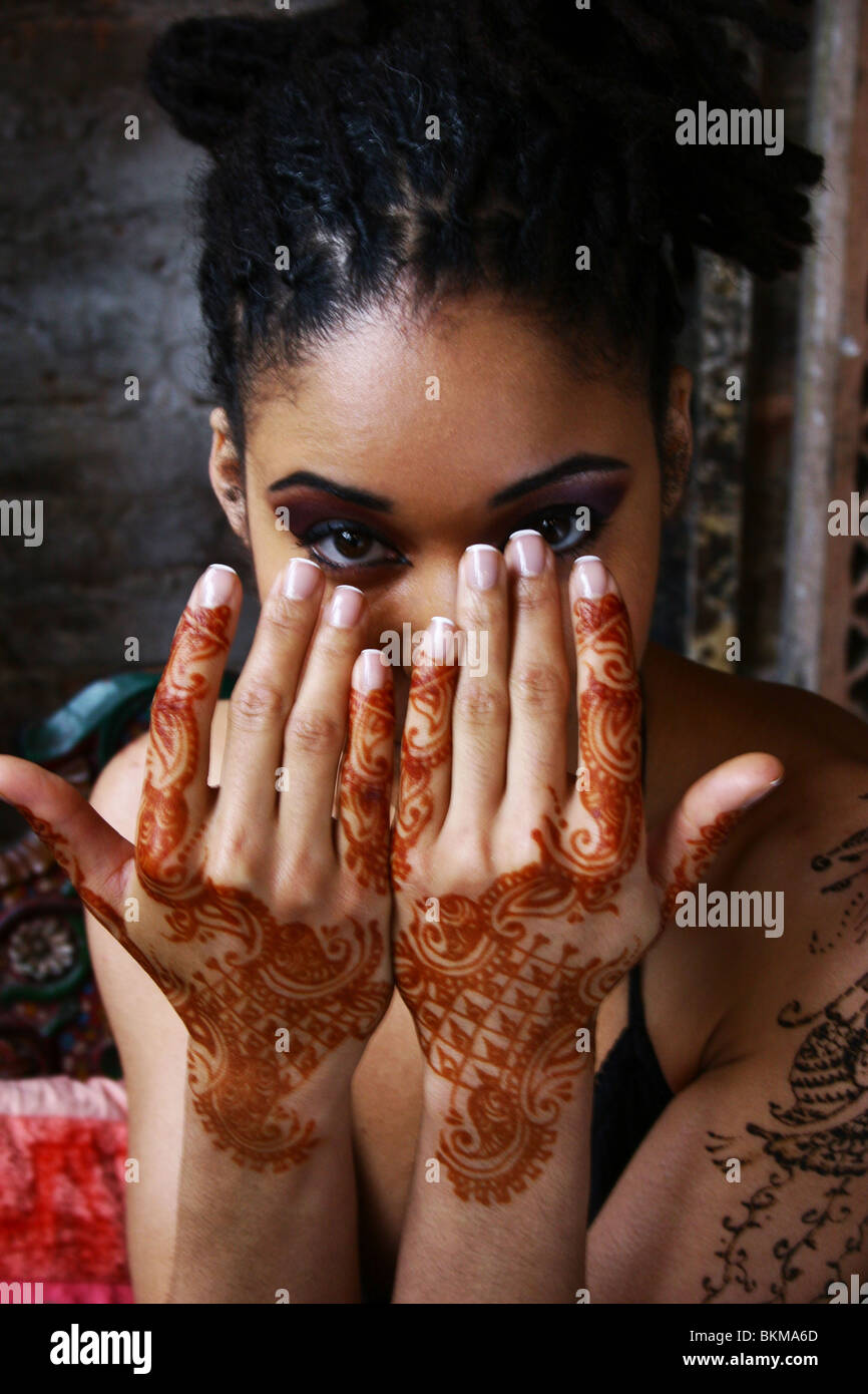 Close up of hands with Moroccan henna temporary tattoo design. - Stock Image