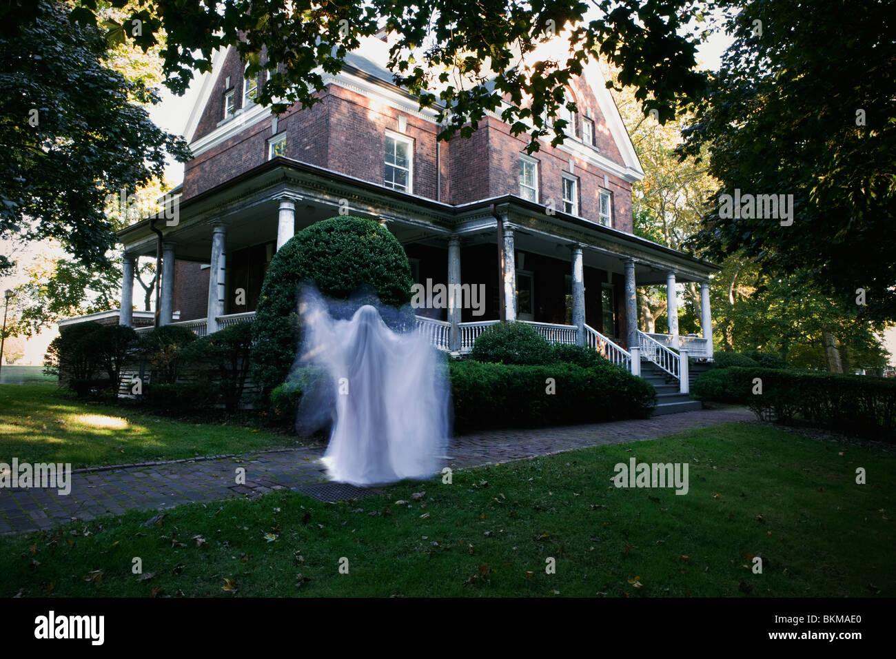 ghostly figure in front of house late afternoon Halloween scary sheet - Stock Image