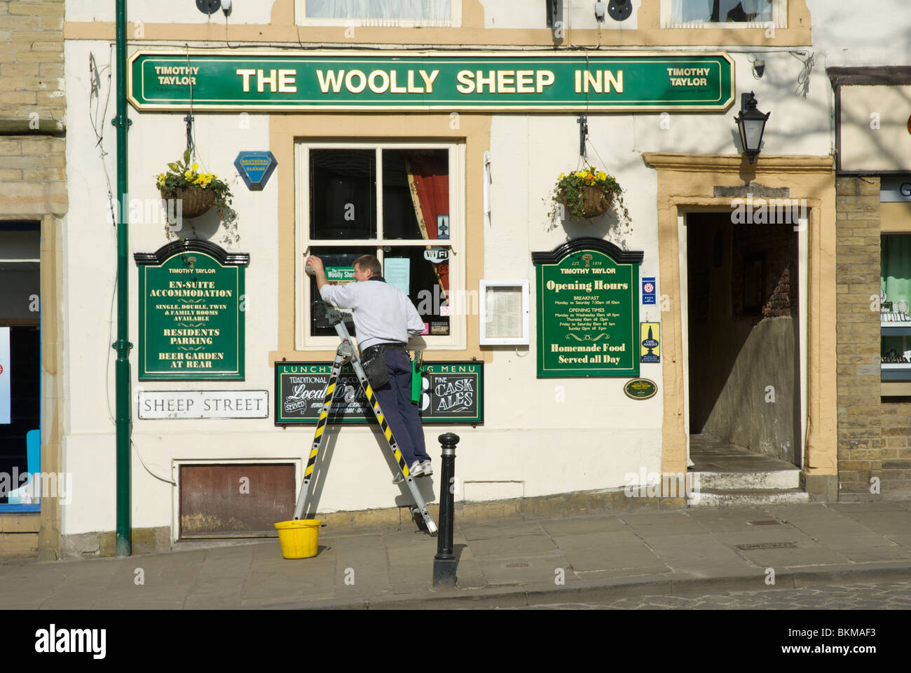 Man washing windows of the Woolly Sheep Inn, on Sheep Street, Skipton, North Yorkshire, England UK - Stock Image
