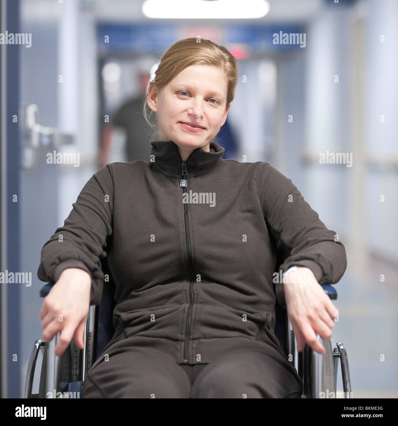 Woman patient in a wheelchair, in a hospital hallway. - Stock Image