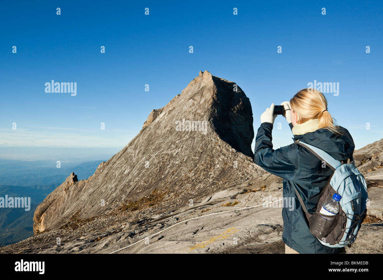 A climber photographs the scenery at the summit of Mt Kinabalu. Kinabalu National Park, Sabah, Borneo, Malaysia. - Stock Image