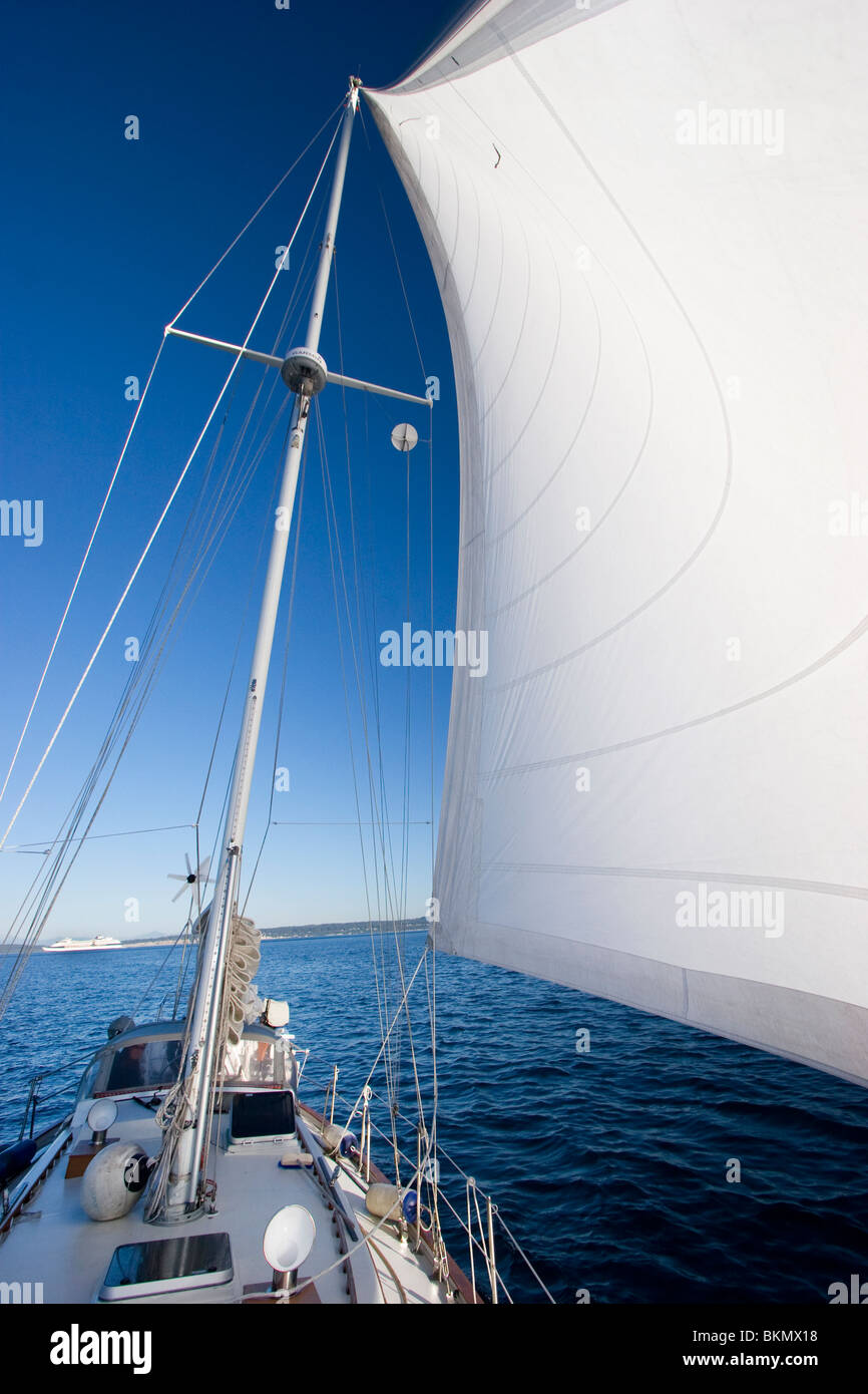 White sail sailboat sailing ocean blue sky - Stock Image