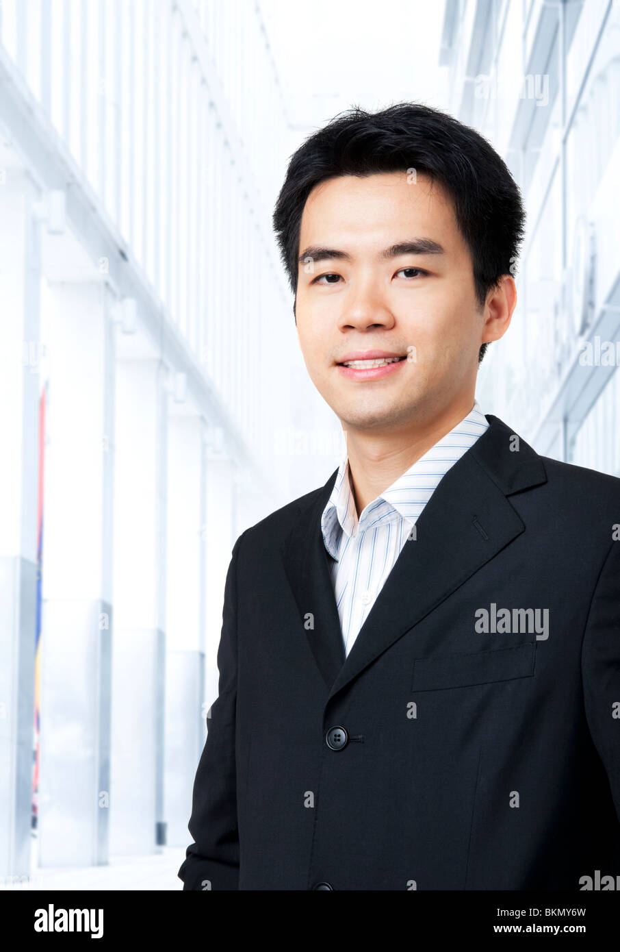 590d81868000 Portrait of young Asian executive in black suit, standing in front of a  modern building