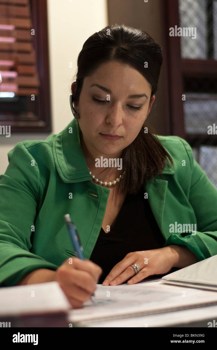 30 year old Hispanic business woman at desk. - Stock Image