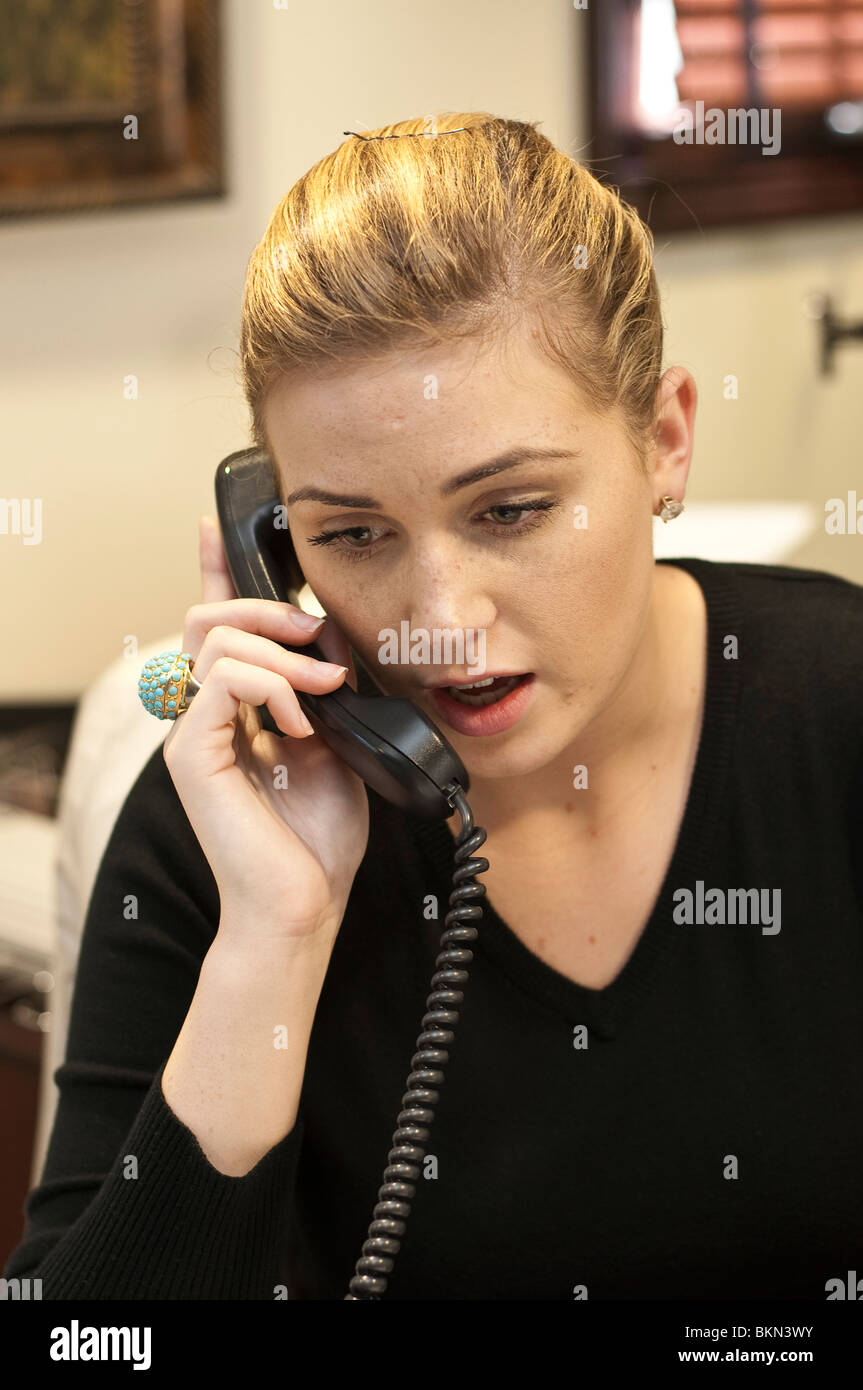 20 - 25 year old white business woman assistant at desk on a phone. - Stock Image