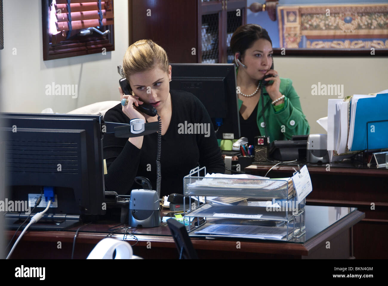 Two 25 - 30 year old woman business assistant women at desk. - Stock Image