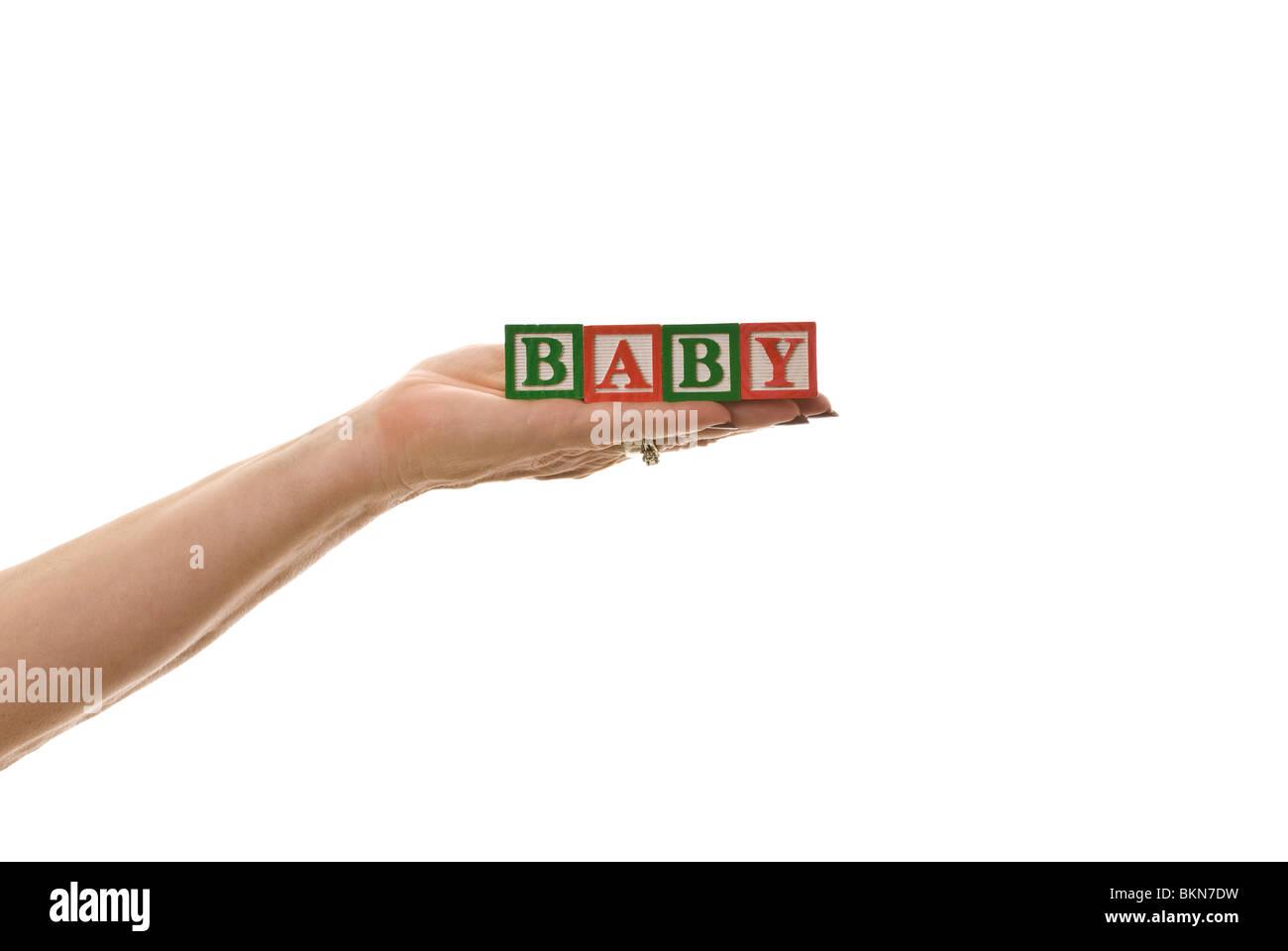 Woman holding children's blocks that spell 'BABY' - Stock Image