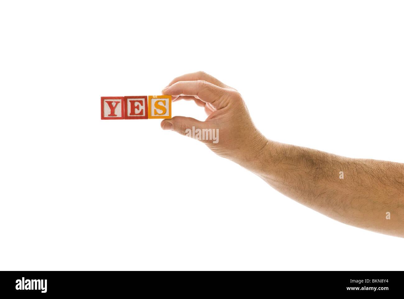 """Man holding children's blocks that spell """"YES"""" Stock Photo"""