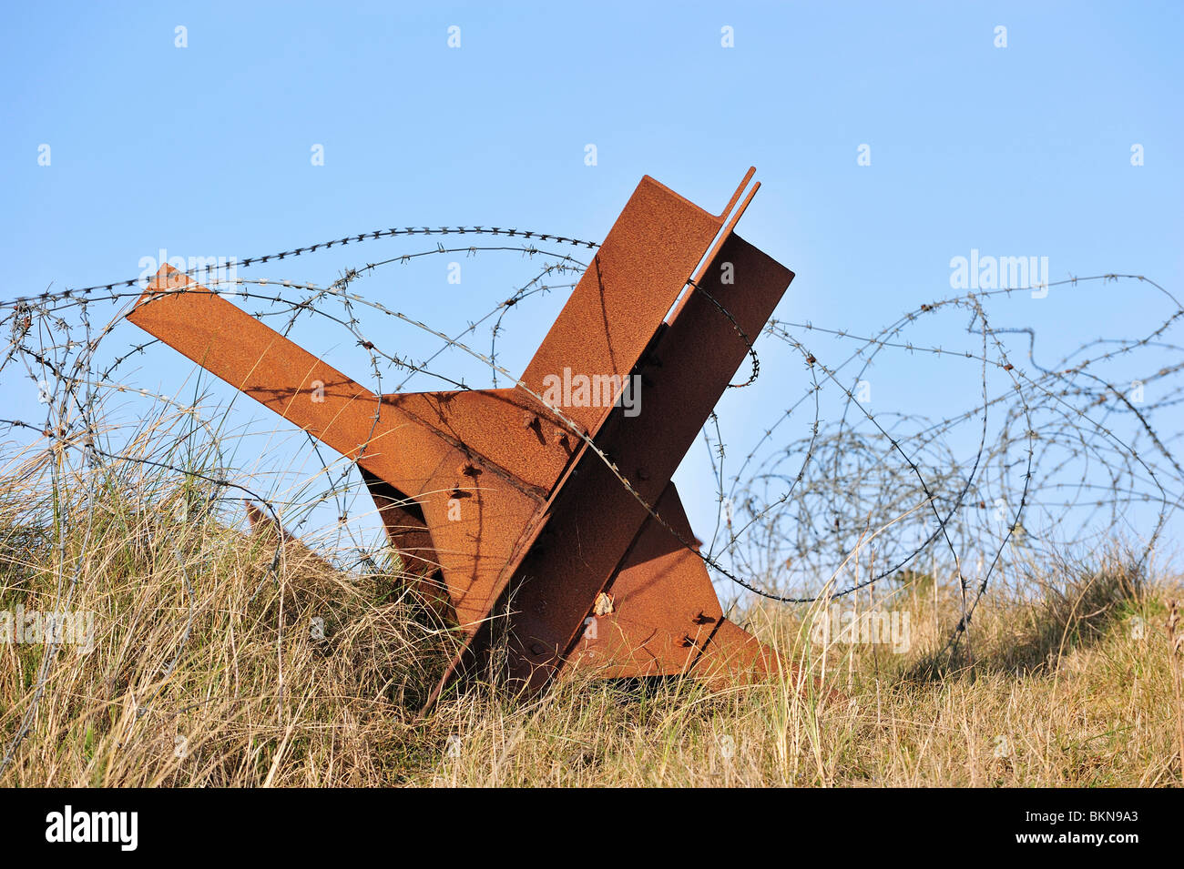 Barbwire and Czech hedgehog, a static anti-tank obstacle defence from WW2 on a Normandy beach along the Atlantik - Stock Image