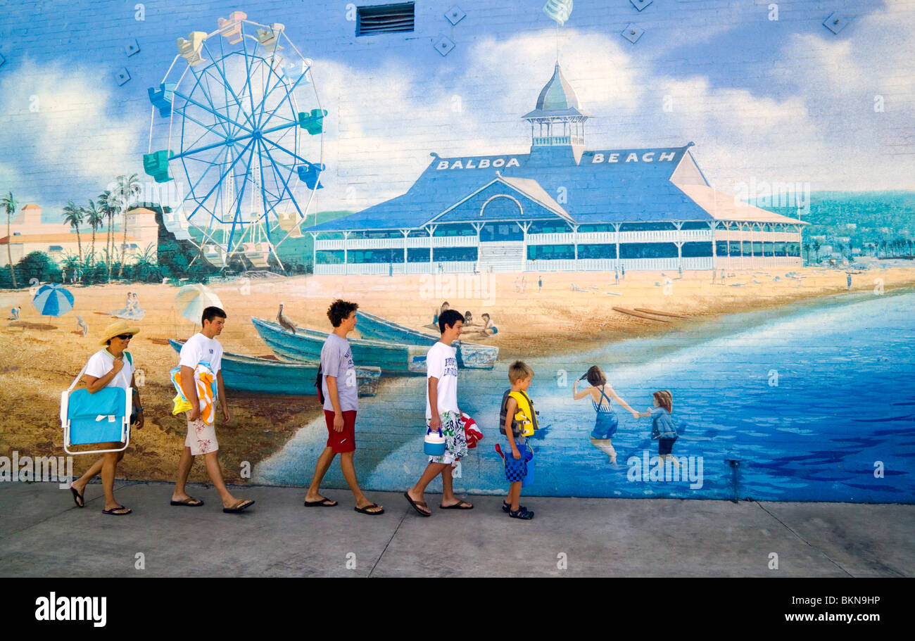 A family walking to the beach passes a wall mural of an early Balboa