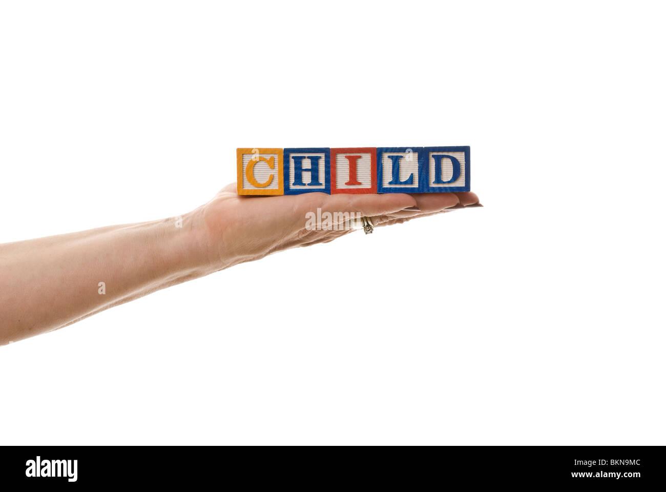 Woman holding children's blocks that spell 'CHILD' - Stock Image