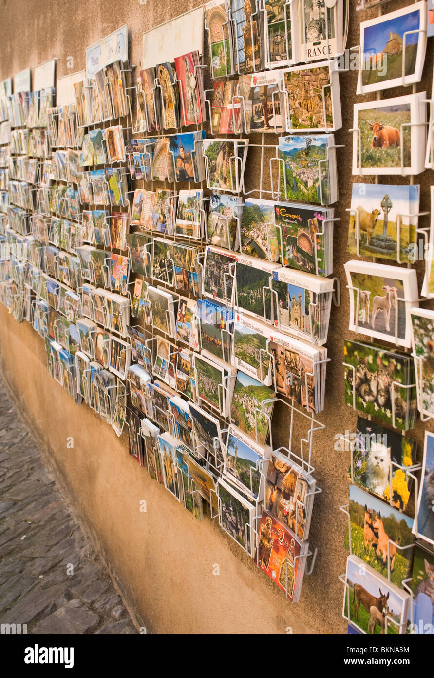 Postcards On Sale in Racks Outside a Gift Shop in Conques Aveyron Midi-Pyrenees France - Stock Image