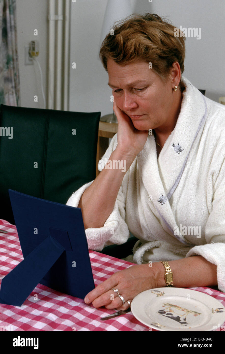 Sad mature woman sit at breakfast table and look at photo in photo frame at the kitchen table. - Stock Image