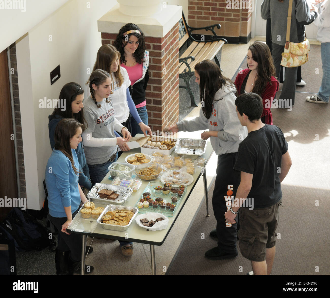 High school students gathering at an after school bake sale fund raiser. - Stock Image