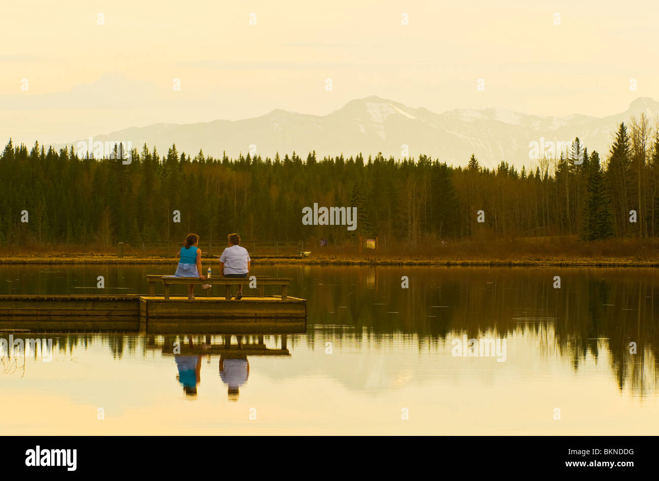 Two women sitting on a dock - Stock Image