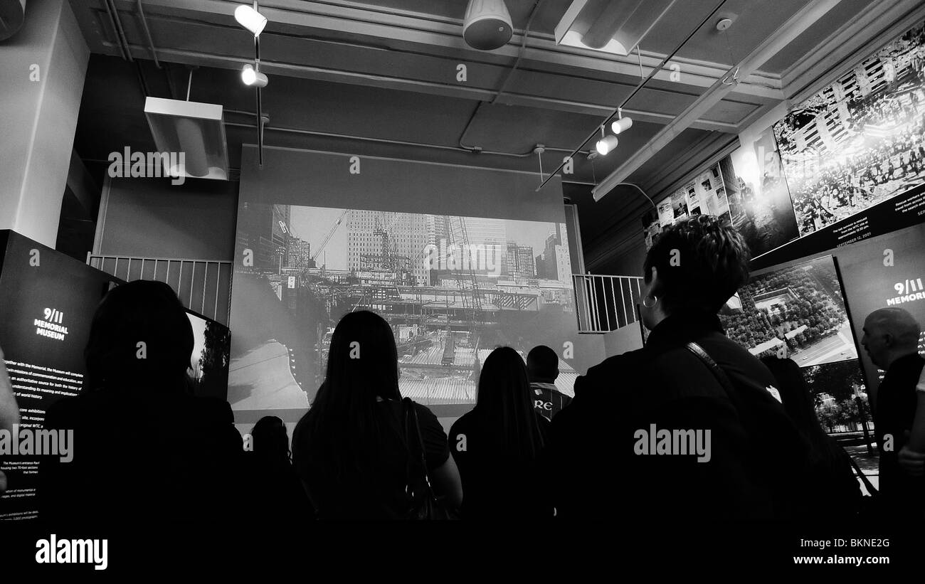 Tourists watching a 911 movie at a New York City interpretive tourism center. - Stock Image