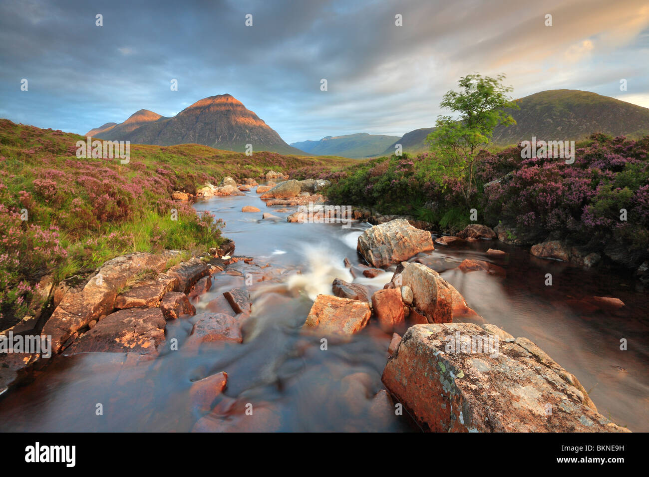 Sun strikes the peak of Stob Deargh over the River Coupall near Glen Etive in the Highlands of Scotland, UK - Stock Image