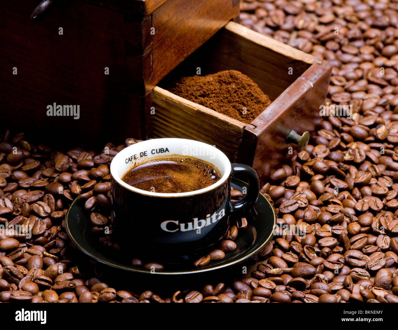 detail of coffee mill with coffee beans and cup of coffee - Stock Image