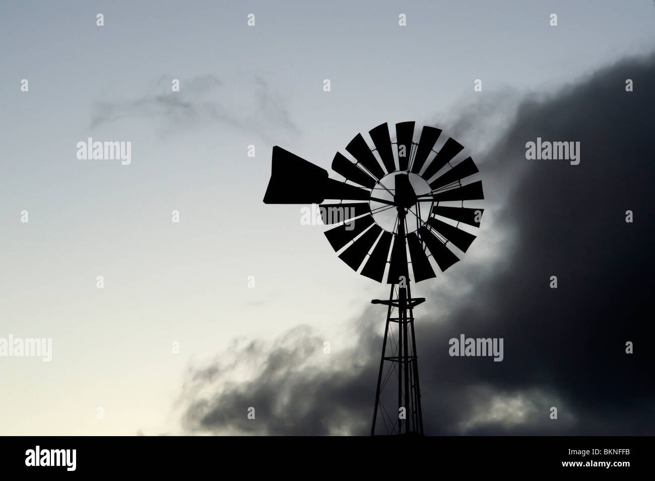 Windmill silhouetted against clouds - Stock Image