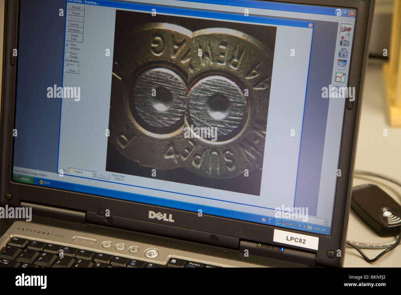 Computer screen showing a side-by-side comparison of hammer marks on two ammunition casings. Nebraska State Patrol Stock Photo