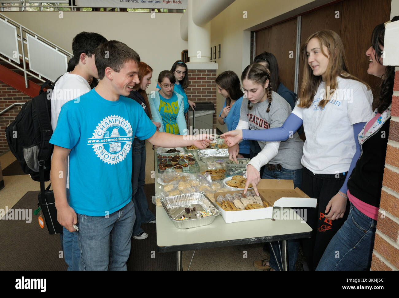 High school students gathering at an after school bake sale fundraiser. - Stock Image